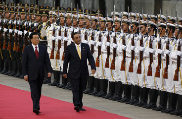 Chinese President Hu walks with his Pakistani counterpart Zardari as they inspect an honour guard during an official welcome ceremony at the Great Hall of the People in Beijing