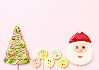Lollipops new year sweets. Candy christmas tree, top view flat lay on pink background. Sweet sucker, lollipop snowman, candy, isolated minimal concept above decoration, new year food background