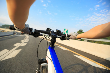 cyclist hands cycling mountain bike on driving road