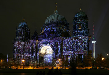 People stand in front of the illuminated Berliner Dom during the Festival of Lights in Berlin
