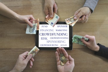 crowdfunding concept with tablet and many hands