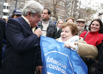 Former President Luis Alberto Lacalle, pre-candidate for the White party for the primaries elections, talks with a supporter before casting his ballot in a voting station in Montevideo