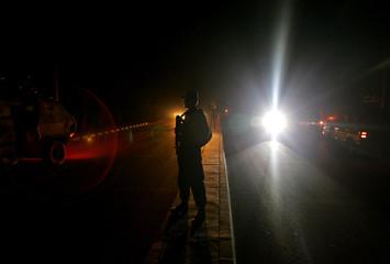 Afghan policeman secures blast site in Kabul