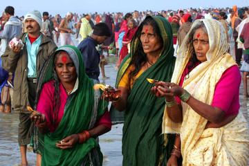 Hindu women pray to the Sun god on a beach at Sagar Island, India.