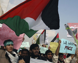 Islamic University students wave Palestinian flags and hold up placards in Islamabad, during a protest rally against the Israeli offensive in Gaza