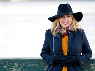 Young woman in hat and coat walking. Portrait of the blonde on the street, smiling and fun
