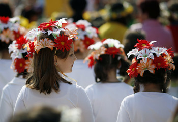 """Girls wear spring flower crowns at a parade druing the """"Tulips festival"""" held to mark the beginning of the spring in Pitesti"""