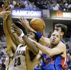INDIANAS RON ARTEST FIGHTS FOR REBOUND WITH DETROITS TAYSHAUN PRINCE AND MEHMET OKUR.