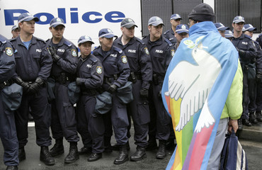 A protester wearing a flag with a picture of a dove of peace on it walks past at line of police during a rally against the Asia-Pacific Economic Cooperation (APEC) summit in Sydney