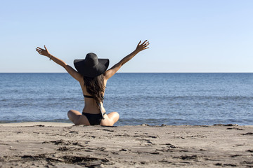Young woman in bikini and black hat on the beach