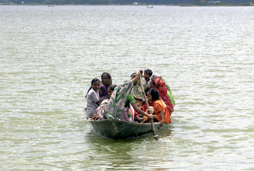 Villagers use a boat to reach a safety during floods at Panikhati village in India.