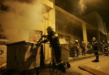 A fireman tries to to extinguish a fire in a garbage bin, during clashes with protesters after a rally, in central Athens