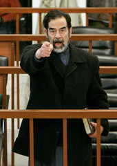 Former Iraqi leader Saddam Hussein gestures during his trial in Baghdad