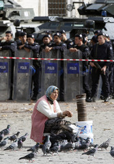 A woman sells feed for pigeons as Turkish riot police stand guard during a protest by university students against Turkey's High Education Board at Beyazit Square in Istanbul