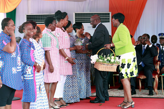 Daniel Kablan Duncan, Ivory Coast's Vice President, distributes lily of the valley flowers to women workers during May Day celebrations in Abidjan