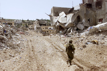 AN ISRAELI SOLDIERS WALKS IN THE DESTROYED JENIN REFUGEE CAMP.