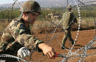 Lebanese soldiers clear away wires as Israeli soldiers in an army vehicle keep watch along the border with Israel in the Khiam valley