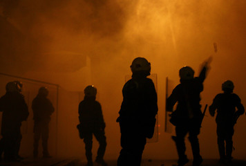 Riot policemen throw tear gas at protesters during riots in Athens