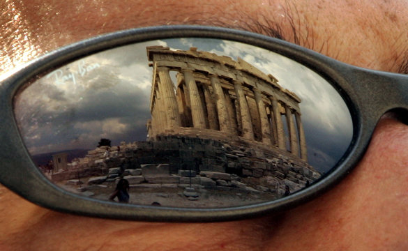 The temple of the Parthenon is reflected in a tourist's sunglasses in Athens.