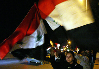 Young Syrians wave their country's national flag at a Damascus street