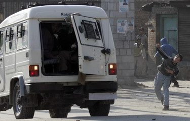 Kashmiri protester throws stones at Indian police vehicle during protest in Srinagar