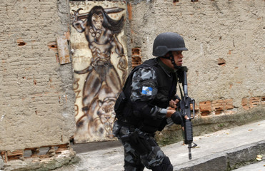 A police officer runs past graffiti as he patrols at Matriz slum in Rio de Janeiro