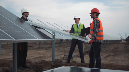 The engineer controls installation process of solar batteries, two employees in a uniform and in hardhat.