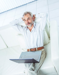 successful businessman working on laptop sitting on sofa in modern office