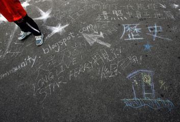 A boy stands near drawings in front of Star Ferry Clock Tower in Hong Kong