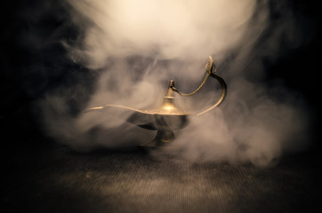 Antique Aladdin arabian nights genie style oil lamp with soft light white smoke, Dark background. Lamp of wishes concept. Toned