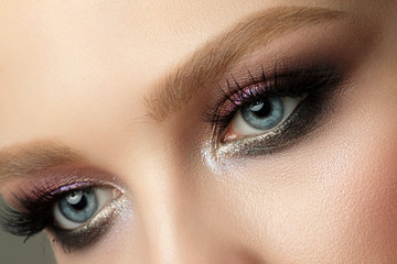 Close up of blue woman eye with smokey eyes makeup