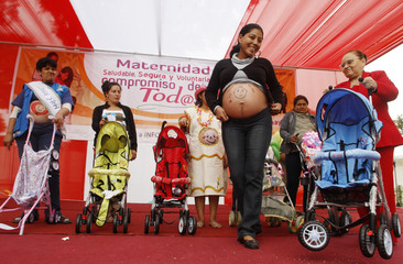 """Winners of """"Beautiful Pregnant Women"""" contest stand on stage with prams awarded to them during an event to celebrate """"Healthy Maternity Week"""" in Lima"""