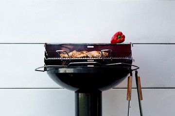 Chicken and red pepper barbecue against a white wall