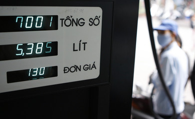 A price board displays the prices of fuel at a petrol station in Hanoi