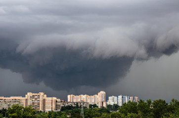Tornado, thunderstorm, funnel clouds over the city.