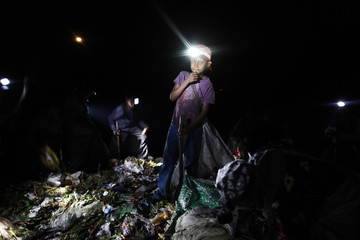 An illegal immigrant boy from Myanmar uses a head lamp to search for plastic at a rubbish dump site near Mae Sot