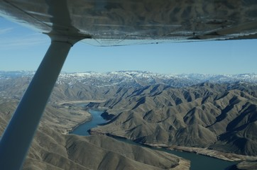 A view of the Boise river and snow capped mountains in the winter from a small airplane. The wing prominently visible in the foreground.