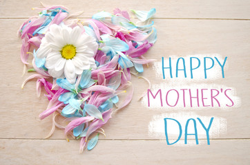 Mother's day greeting concept. Love symbol on wooden background maid by blue and pink petals with daisy flower.