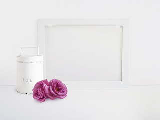 White blank wooden frame mockup with old tin and pink rose flowers lying on the table. Poster product design. Styled stock feminine photography. Home decor.