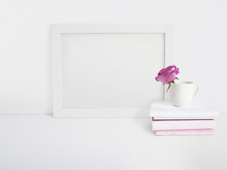 White blank wooden frame mockup with a rose flower in a porcelain cup and pile of books lying on the table. Poster product design. Styled stock feminine photography. Home decor.