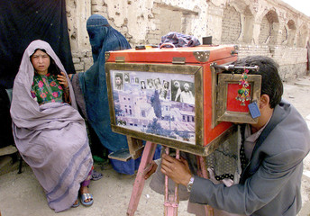 An Afghan photographer uses an old-fashioned box camera to take a picture of an Afghan woman in Kabu..
