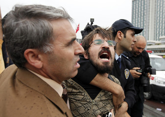 Policemen detain a protester during a rally against the IMF in Istanbul