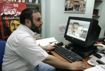 Bassam Qantar, the brother of Samir Qantar, downloads pictures of his brother in Beirut