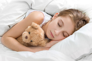 child hugging her teddy bear in sleep