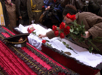 The hat of sailor Victor Kuznetsov lies on his coffin as unidentified mourner puts flowers on the bo..