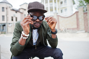 Close up portrait of stylish african american man wear on sunglasses and cap outdoor. Street fashion black man.