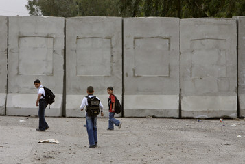 Schoolboys walk along a concrete wall on a street in Adhamiya district in Baghdad