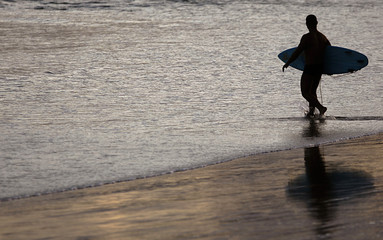 A surfer walks on Joaquina Beach during sunset where the Nova Schin Festival takes place in Florianopolis