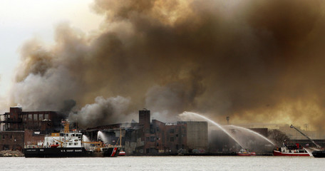 Smoke rises from a fire at a waterfront warehouse in Brooklyn, New York  May 2, 2006. The blaze, whi..