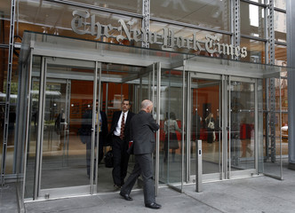 People leave the New York Times building at 8th Avenue and 41st Street in New York